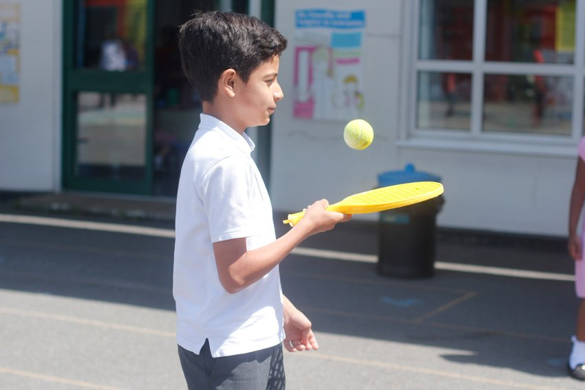Boy playing with a bat and ball in the playground
