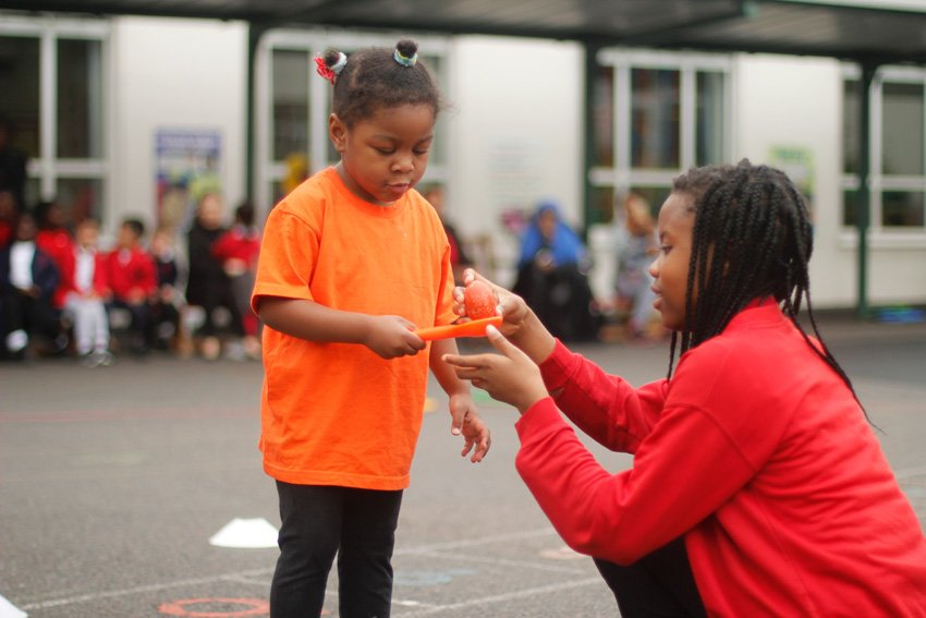 Older girl helping a young girl in an egg and spoon race