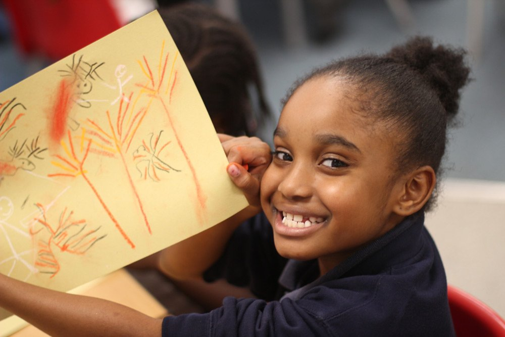 Girl showing off her art during a lesson